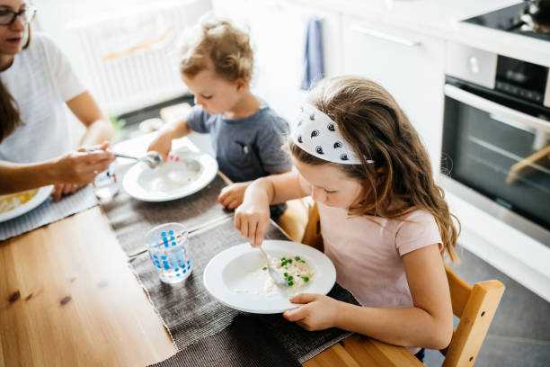 young brother and sister eating lunch together in kitchen - child eating appetite  stock pictures, royalty-free photos & images