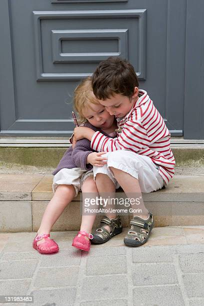 Young brother and sister embracing outdoors