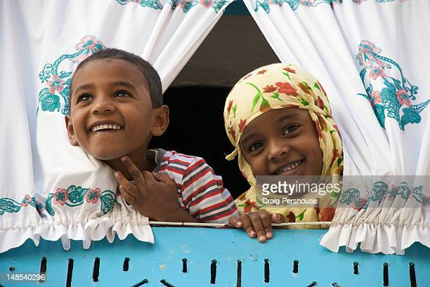 Young brother and sister looking through curtains over upstairs window of their house.