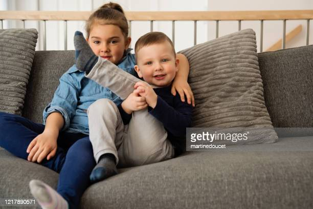 """young brother and sister on a sofa at home. - """"martine doucet"""" or martinedoucet stock pictures, royalty-free photos & images"""