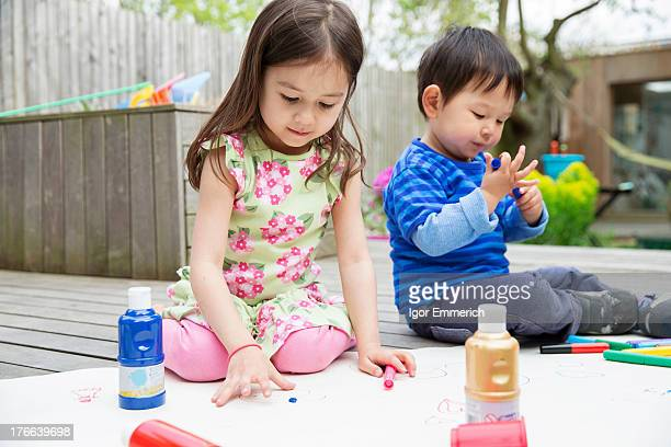 Young brother and sister painting and drawing in garden