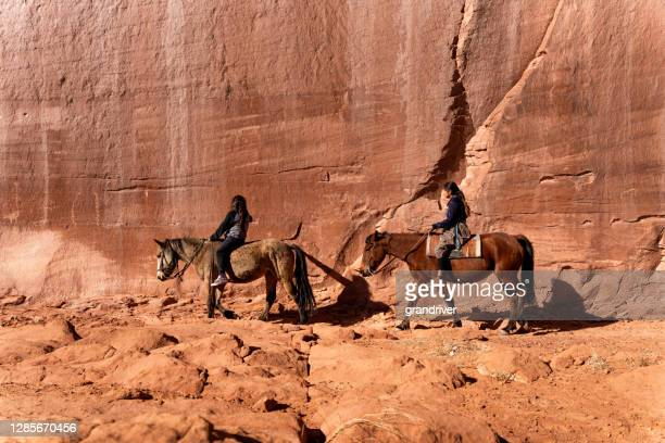 a young brother and sister ride their horses by a massive rock wall filled with native petroglyphs in monument valley, arizona - apache stock pictures, royalty-free photos & images