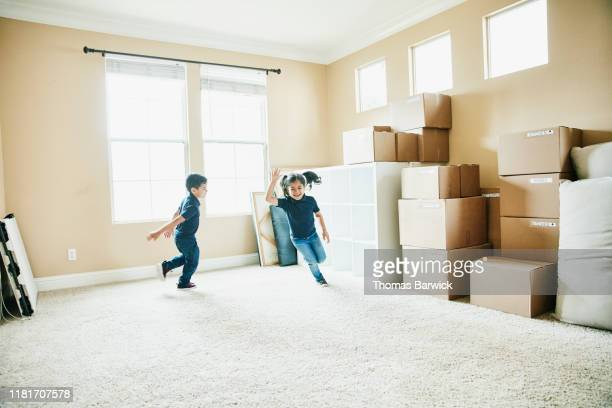 young brother and sister running in living room filled with boxes on moving day - rennen körperliche aktivität stock-fotos und bilder