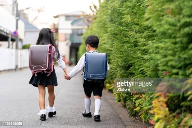 jeune frère et soeur marchant à l'école ensemble retenant des mains - écolière photos et images de collection