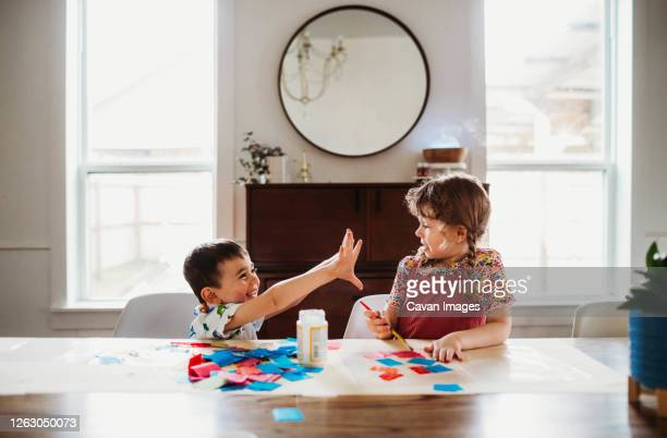 young brother showing sister messy hands with doing a craft - art and craft stock pictures, royalty-free photos & images