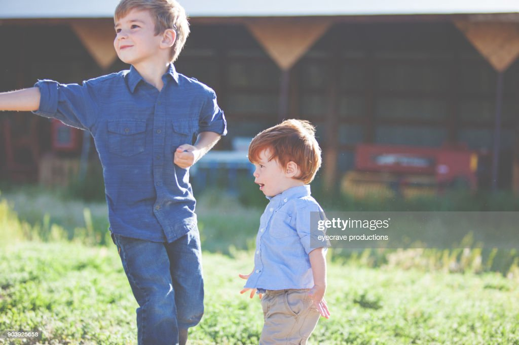 Young Brothers Outdoors in Summer Having Fun Playing : Stock Photo