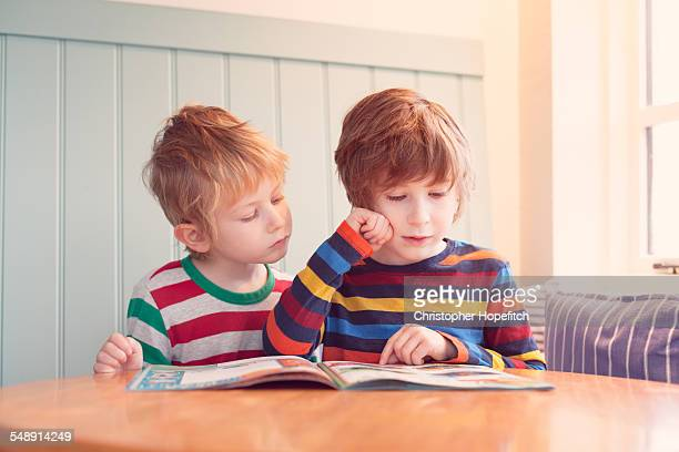 young brothers reading - magazine stock pictures, royalty-free photos & images