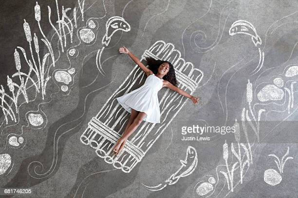 "young brown girl ""floats"" on chalkboard raft - bottomless girl stock pictures, royalty-free photos & images"