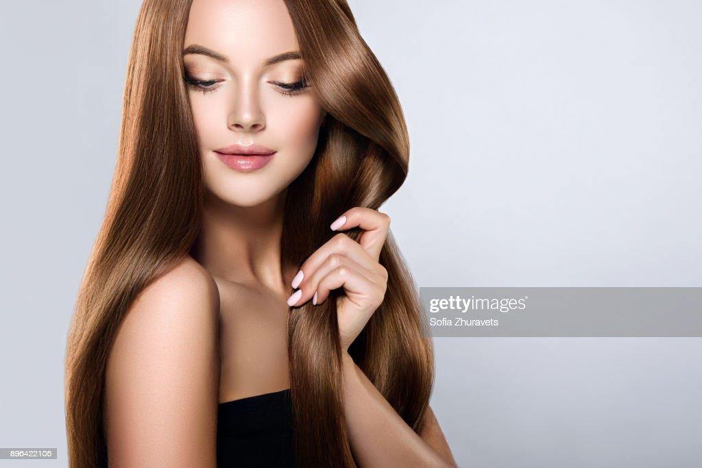 若い、髪の長い、まっすぐ、よく手入れをされた茶色の髪の美しいモデルの優しさと自分の髪に触れています。 : ストックフォト