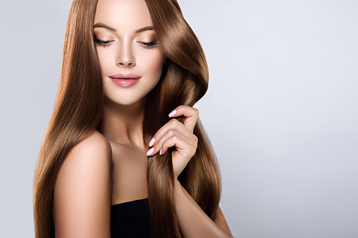 Young, brown haired beautiful model with long,  straight, well groomed hair is touching own hair with tenderness. 896422106