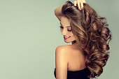 Young, brown haired woman is touching softly owne hair. Hair care.