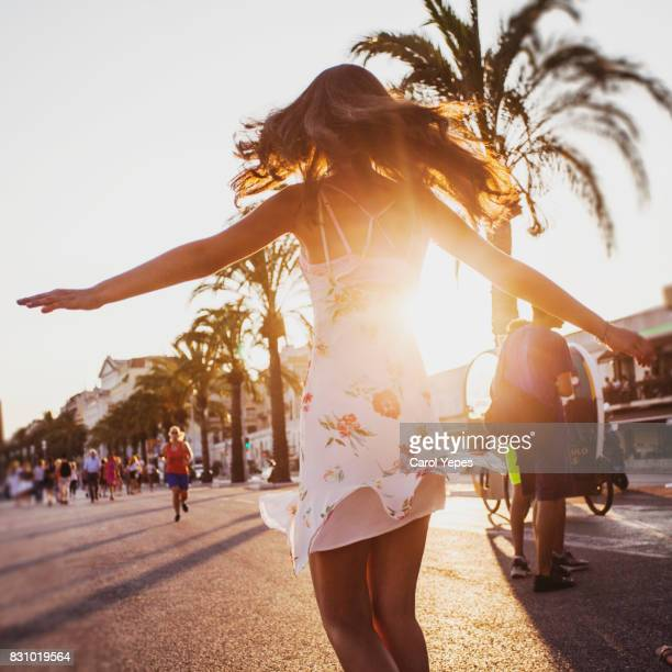 young brunette dancing outdoor at sunset