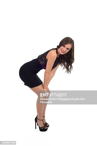 Young Brunette Female in Black Dress Bending Over