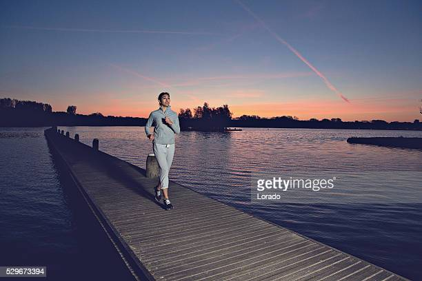 Young brunette female jogging at dawn on lakeside pier
