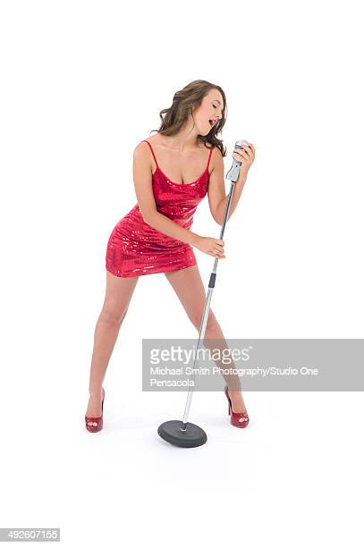 young brunette female singing with a microphone - microphone stand stock photos and pictures