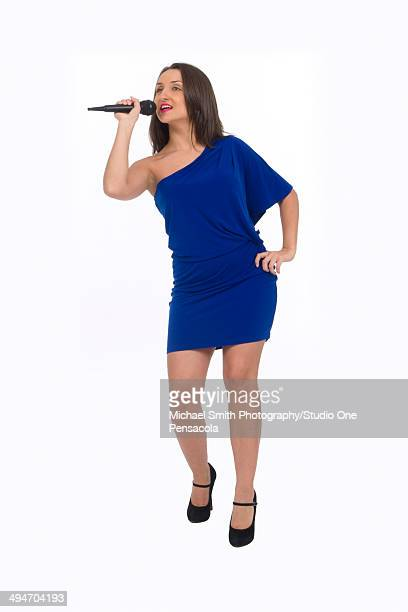 young brunette female singing with a microphone - アシメトリードレス ストックフォトと画像
