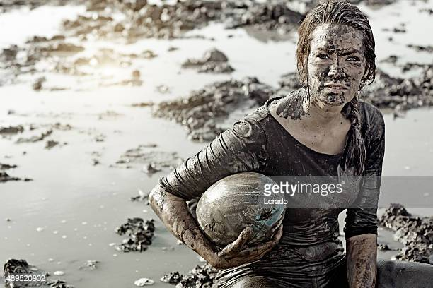 Young brunette female sitting during a mud run