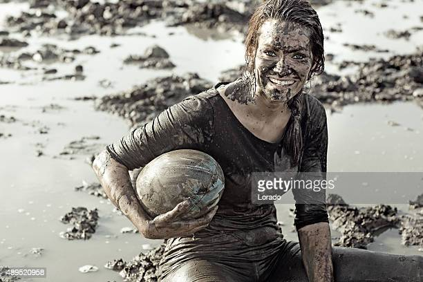 Young brunette female smiling during a mud run