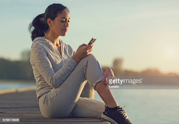 Young brunette female using smartphone at lakeside pier