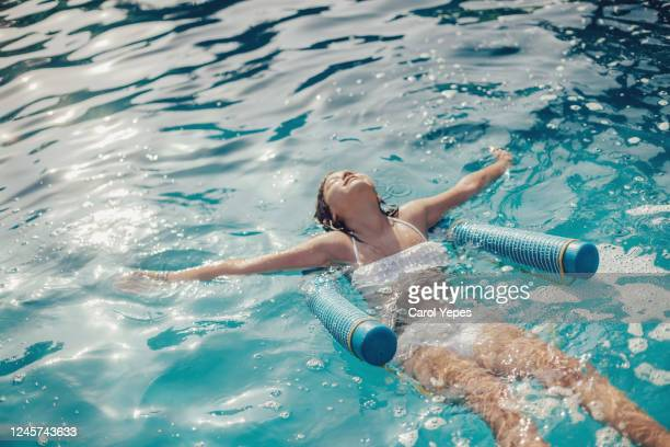 young brunette girl relaxing floating at pool - sun lounger stock pictures, royalty-free photos & images