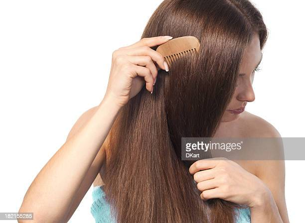 Young brunette lady combing her long hair with a wooden comb