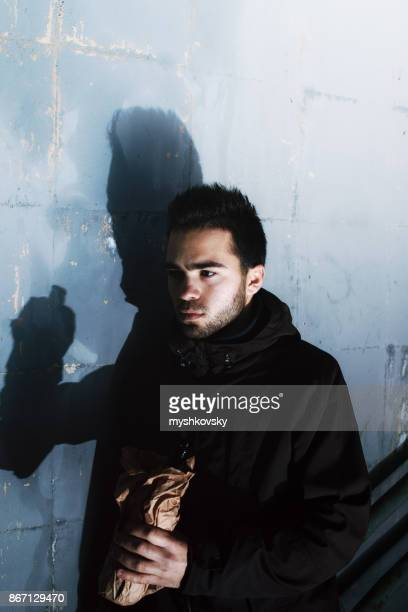Young brunette man alcoholic in the underpass