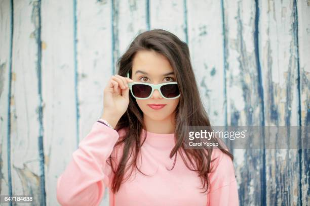 young brunette peeking over sunglasses