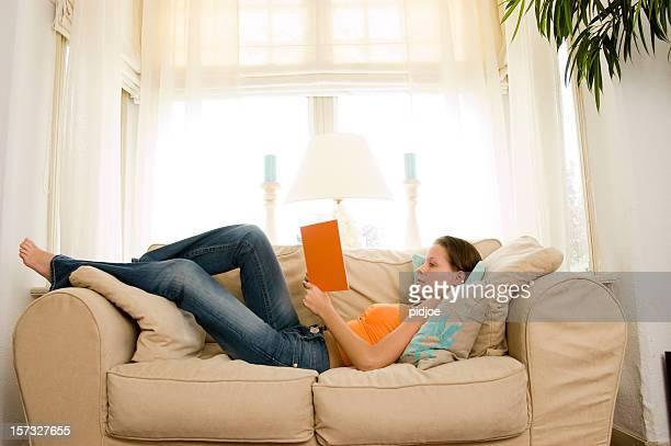 Jeune brunette lisant un livre sur le canapé-lit