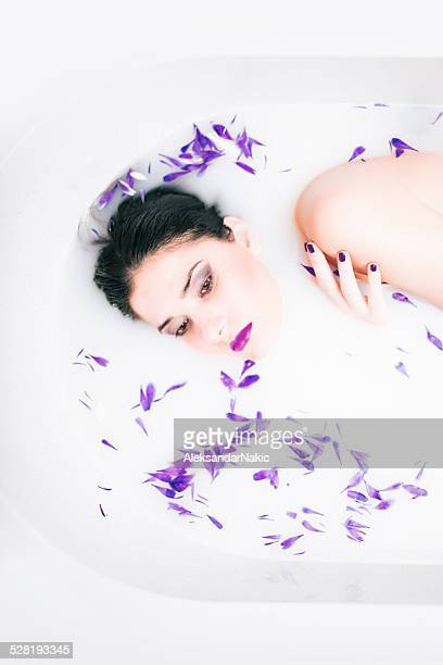 Jeune brunette se détendre dans le bain de lait