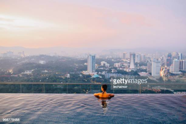 young brunette relaxing in the pool as the sun sets above kuala lumpur, malaysia - luxury hotel stock pictures, royalty-free photos & images