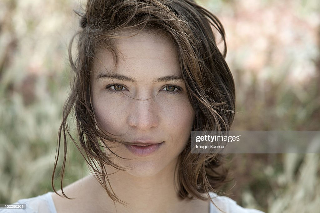 Young brunette woman alone outdoors, portrait : Stock Photo