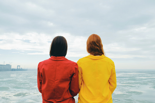 Young brunette woman and red-haired woman on the background of a cloudy sky, the sea with ice and hydroelectric station. Apocalypse. - gettyimageskorea