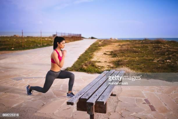 atleta jovem morena fazendo lunges ao ar livre - flexionando perna - fotografias e filmes do acervo