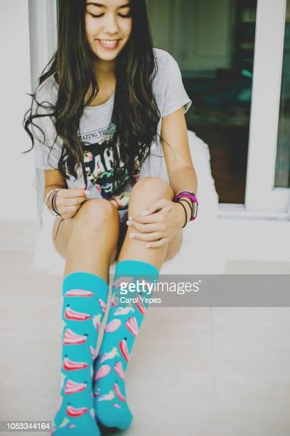 young brunette woman in blue socks at home - piernas bonitas de mujer fotografías e imágenes de stock