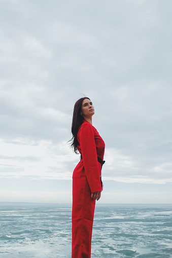 Young brunette woman in red suit against the sky and river with ice - gettyimageskorea