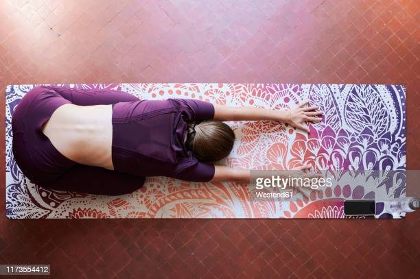 young brunette woman practising yoga in student dorm, child position from above - yogi stock pictures, royalty-free photos & images