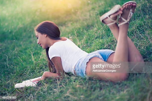 Young Brunette Woman Reading Book in the Nature
