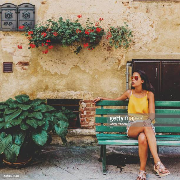 young brunette woman sitting on green bench on siena,tuscany,italy - siena italy stock photos and pictures
