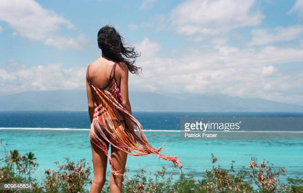 young brunette woman stands high up confidently overlooking blue clear water tropical ocean with hair flowing - femme tahitienne photos et images de collection