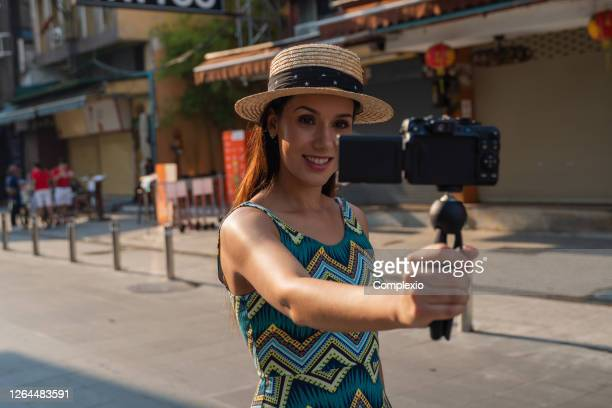 携帯電話を使用して若いブルネットの女性は魅力的な笑顔でセルフビデオ自分撮りを取ります。 - 三脚 ストックフォトと画像