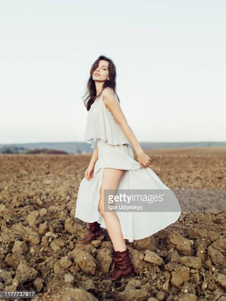 young brunette woman walking in field - white dress stock pictures, royalty-free photos & images