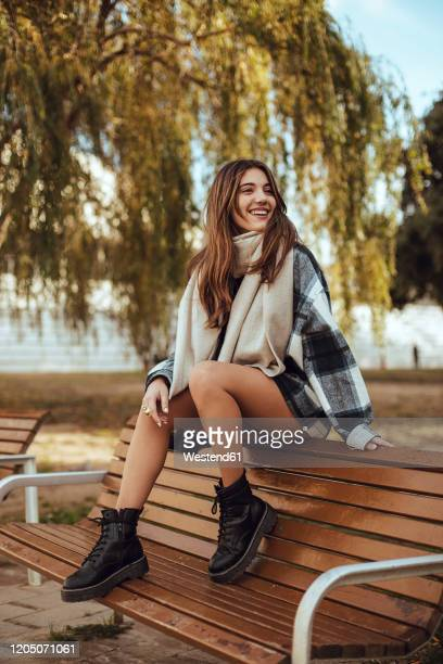 young brunette woman wearing black and white coat and scarf in the city - plaid shirt stock pictures, royalty-free photos & images
