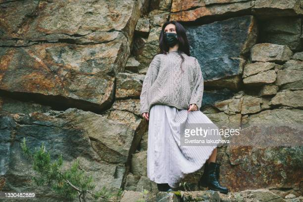 a young brunette woman with long hair in a long silver skirt and a sweater poses at the camera in a black medical mask on the background of a stone slope. masked travel during the coronavirus pandemic. - silver skirt stock pictures, royalty-free photos & images