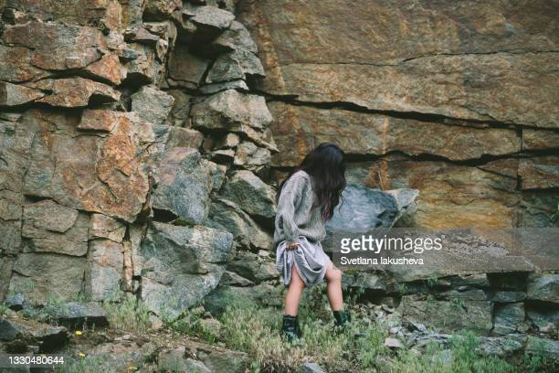 a young brunette woman with long hair in a silver long skirt and a sweater climbs a stone slope. - silver skirt stock pictures, royalty-free photos & images