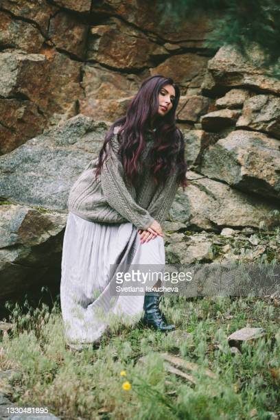 a young brunette woman with long hair in a silver long skirt and a sweater stands near a stone slope wall, posing at the camera, raising her hands to her face, looking into the distance, enjoying nature and enjoying life - silver skirt stock pictures, royalty-free photos & images