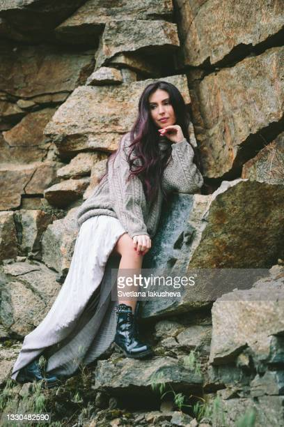 a young brunette woman with long hair in a silver long skirt and a sweater sits on a stone right next to a stone slope wall, rests, enjoys nature and enjoys life - silver skirt stock pictures, royalty-free photos & images