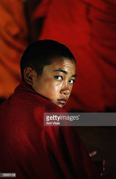 Young Buddhist monk cloaked in his saffron robe prays in the Thiksey monastery August 22, 2003 about 18 kilometers from Leh, the capital of Ladakh,...