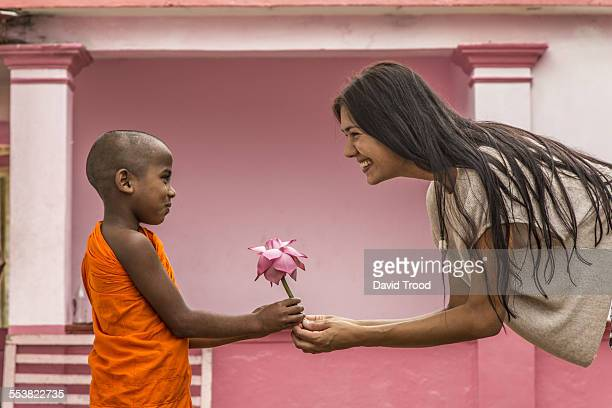 young buddhist monk giving lotus flower to tourist - cultures stock pictures, royalty-free photos & images
