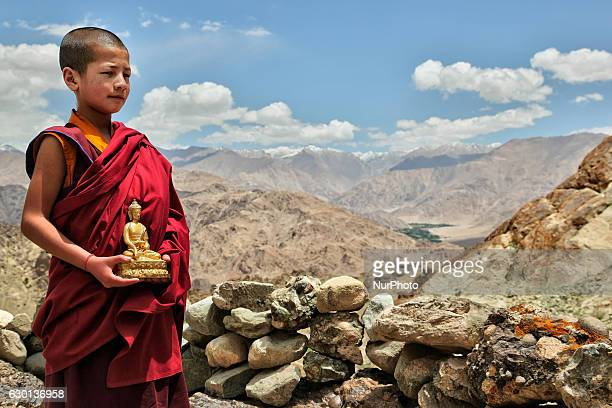 Young Buddhist monk holding a small golden Buddha statue at the Hemis Monastery in Hemis, Ladakh, Jammu and Kashmir, India. Behind are the...