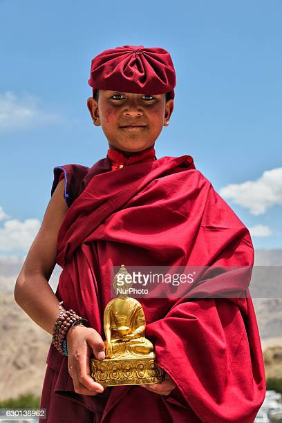 Young Buddhist monk holding a small golden Buddha statue at the Hemis Monastery in Hemis Ladakh Jammu and Kashmir India Behind are the magnificent...
